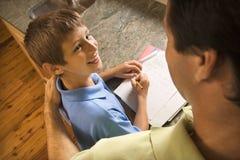 Filho de ajuda do paizinho com trabalhos de casa. foto de stock