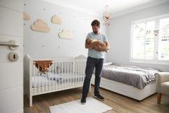 Filho de Comforting Newborn Baby do pai no berçário fotos de stock