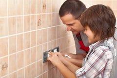 Filho de ensino do pai do eletricista como instalar o soquete bonde Imagens de Stock