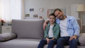 Filho de sorriso feliz do paizinho e da estudante que senta-se no sofá, olhando à câmera, família filme