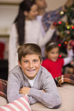 Filho de sorriso que inclina-se no sofá Fotografia de Stock Royalty Free