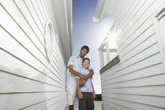 Filho de Standing Arm Around do pai no corredor estreito entre casas Fotografia de Stock Royalty Free