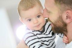 Filho do bebê nos braços de seu pai que afaga Fotografia de Stock Royalty Free
