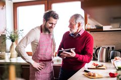 Filho do moderno com seu pai superior com a tabuleta na cozinha Fotografia de Stock