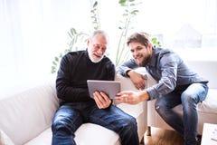 Filho do moderno e seu pai superior com tabuleta em casa Imagens de Stock Royalty Free