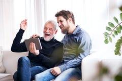 Filho do moderno e seu pai superior com tabuleta em casa Imagem de Stock Royalty Free