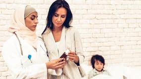 Filho doente de Giving Medicine Mom do pediatra árabe imagem de stock royalty free