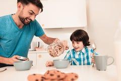 Filho e pai de sorriso Have Breakfast na cozinha imagem de stock royalty free