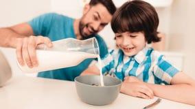 Filho e pai de sorriso Have Breakfast na cozinha fotos de stock royalty free