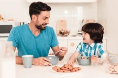 Filho e pai de sorriso Have Breakfast na cozinha imagens de stock royalty free