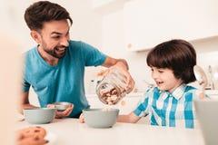 Filho e pai de sorriso Have Breakfast na cozinha fotografia de stock