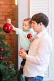 Filho e paizinho que decoram a árvore de Natal em casa na sala de visitas Fotos de Stock Royalty Free