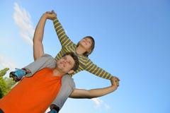 Filho feliz nos ombros do pai fotografia de stock