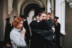 filho hugs pais Felicitações estudante imagem de stock royalty free