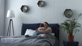 Filho loving que abraça sua mãe na cama após acordado video estoque