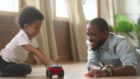 Filho pequeno bonito do africano feliz que joga carros do brinquedo com paizinho video estoque