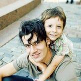 Filho pequeno com o pai no fim de aperto feliz da cidade que sorri acima foto de stock