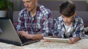 Filho pequeno que joga na tabuleta no assoalho em casa quando paizinho que trabalha no portátil filme