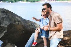 filho que aponta em algo genar perto do rio foto de stock