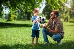 filho que dá a bola do futebol para genar imagem de stock