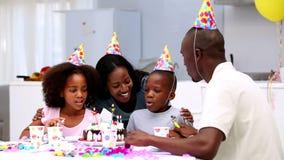 Filho que funde para fora as velas no bolo de aniversário filme
