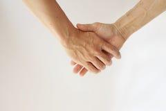 Filho que guarda a mão da mamã no fundo branco Fotografia de Stock Royalty Free