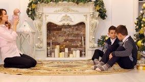 Filhos doces dos tiros da mulher e da mãe no dispositivo para a memória, sentando-se no assoalho na sala de visitas, decorada por filme