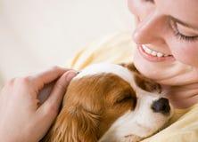 Filhote de cachorro da terra arrendada da mulher nova no sofá foto de stock royalty free