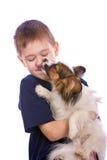 Filhote de cachorro que lambe a face da criança Imagens de Stock Royalty Free