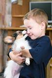 Filhote de cachorro que lambe a face dos childs imagem de stock