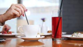 Filiżanka coffe i szkło napój na stole Kobiety ręka bierze cukier i stawia je w filiżance, inna kobieta zbiory wideo