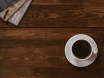 Filiżanka czarna kawa na brązu drewnianym stole z moda magazynem Pisze przerób, filmu skutek, depresja klucz zdjęcia stock
