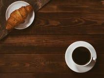 Filiżanka czarna kawa na brązu drewnianym tle z croissant Pisze przerób, filmu skutek, depresja klucz fotografia stock