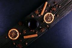 Filiżanka kawy, gwiazdowy anyż, cynamon, wysuszone fasole na ciemnym kuchennym countertop, pomarańczowe i kawowe Fragrant pikantn obrazy royalty free