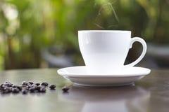 Filiżanka świeża kawa z kawowymi fasolami na drewnianym stole Zdjęcia Stock