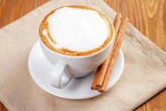 Filiżanka świeżo robić cappuccino z cynamonowymi kijami fotografia royalty free