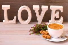 Filiżanka aromat kawa z coockees, kwiaty i słowo miłość na lekkim drewnianym tle szczęśliwy dzień valentine s obraz stock
