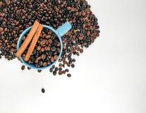 Filiżanka błękitna kawa z kawowymi fasolami otacza i dwa cynamonowego kija z pustą przestrzenią, Odg?rny widok fotografia royalty free