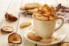 Filiżanka batożący kremowi kawowi i jabłczani ciastka na drewnianym stole obrazy royalty free