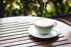 Filiżanka biała kawa umieszcza na brown drewnianym stole i jest p Obrazy Royalty Free