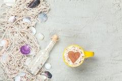 Filiżanka, butelka i sieć z skorupami na piasku, Obrazy Royalty Free