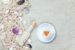 Filiżanka, butelka i sieć z skorupami na piasku, Zdjęcia Stock