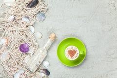 Filiżanka, butelka i sieć z skorupami na piasku, Zdjęcie Royalty Free
