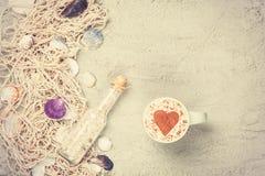 Filiżanka, butelka i sieć z skorupami na piasku, Zdjęcie Stock