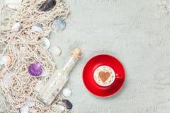 Filiżanka, butelka i sieć z skorupami na piasku, Obrazy Stock