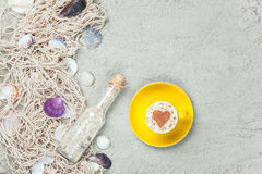 Filiżanka, butelka i sieć z skorupami na piasku, Obraz Stock
