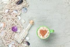 Filiżanka, butelka i sieć z skorupami na piasku, Zdjęcia Royalty Free
