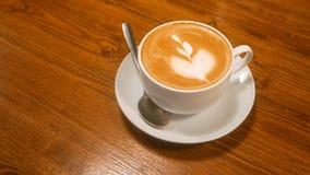Filiżanka cappuccino kawa na brown drewnianym stole nad narzędzie błękitny stonowany widok Zdjęcia Stock