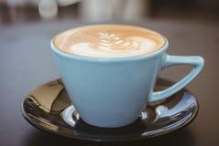 Filiżanka cappuccino z kawową sztuką na drewnianym stole zdjęcia stock
