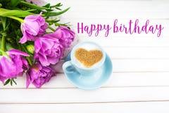 Filiżanka cappuccino z kierowym kształtnym symbolem i purpurowi tulipany na drewnianej inskrypcji wszystkiego najlepszego z okazj fotografia royalty free